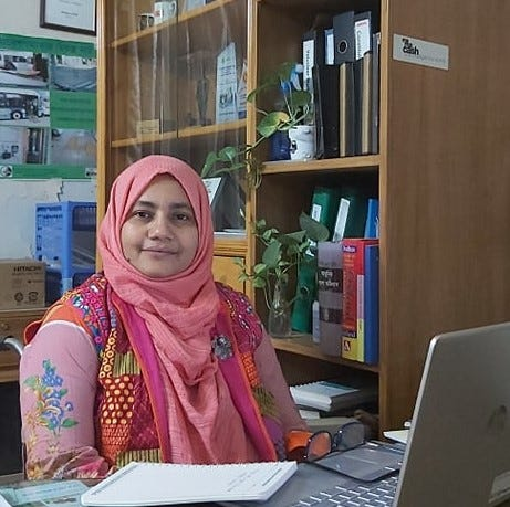Misti sits in her office, looking towards camera she wears a pink headscarf and a colourful pink top. Her laptop frames the foreground and a filing cabinet with files and plants the background.