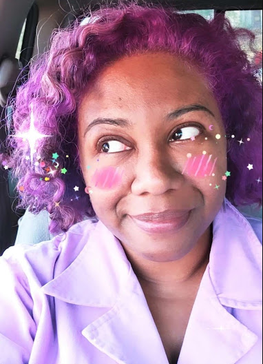 Selfie of Patricia. Her hair is bright purple and she is looking off to the side. She is wearing a lavender jumpsuit but the image is only from the chest upward. There is a filter applied that makes her have pink cheeks and glittery stars around her face.