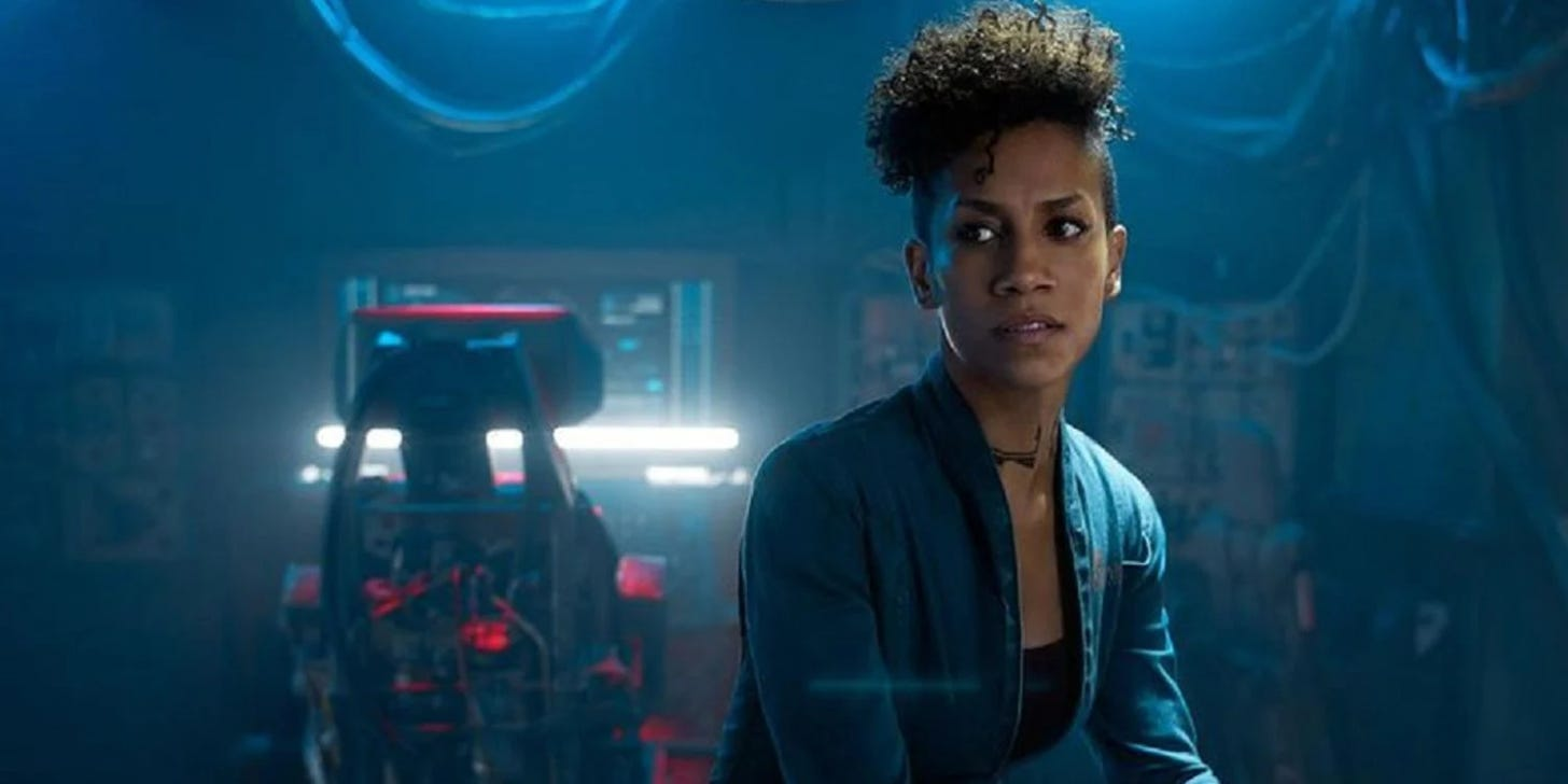 Naomi Nagata from The Expanse sitting in her ship, with a work station in the background behind her