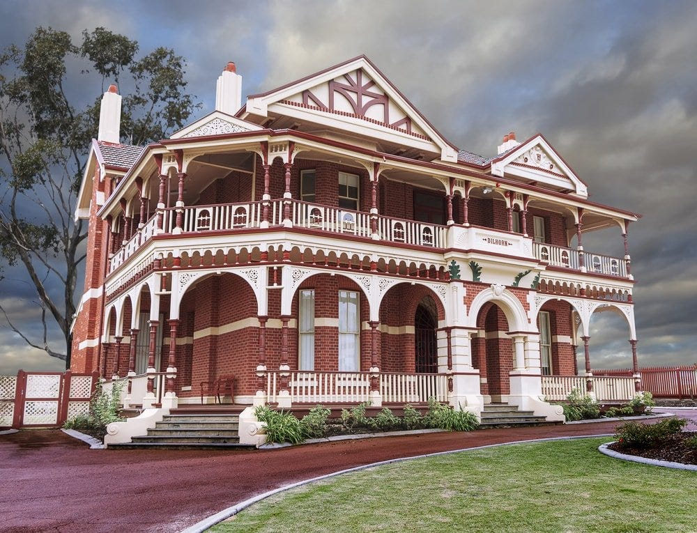 This is a red Quuen Anne Victorian home with wrap-around porch and arches.