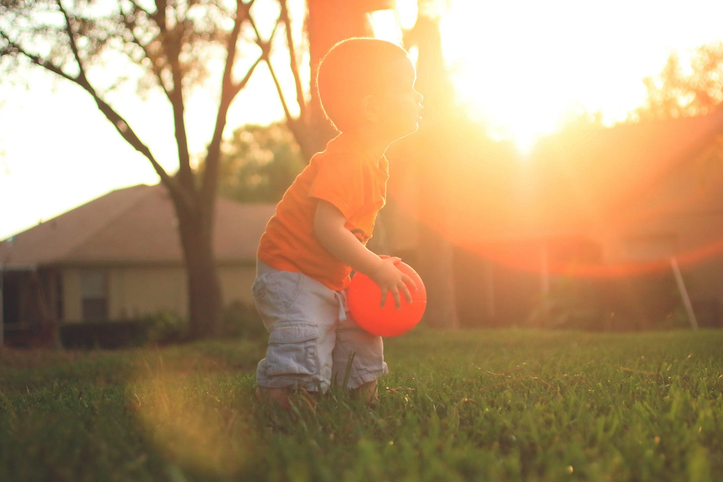 young boy playing ball in the yard for article by Larry G. Maguire