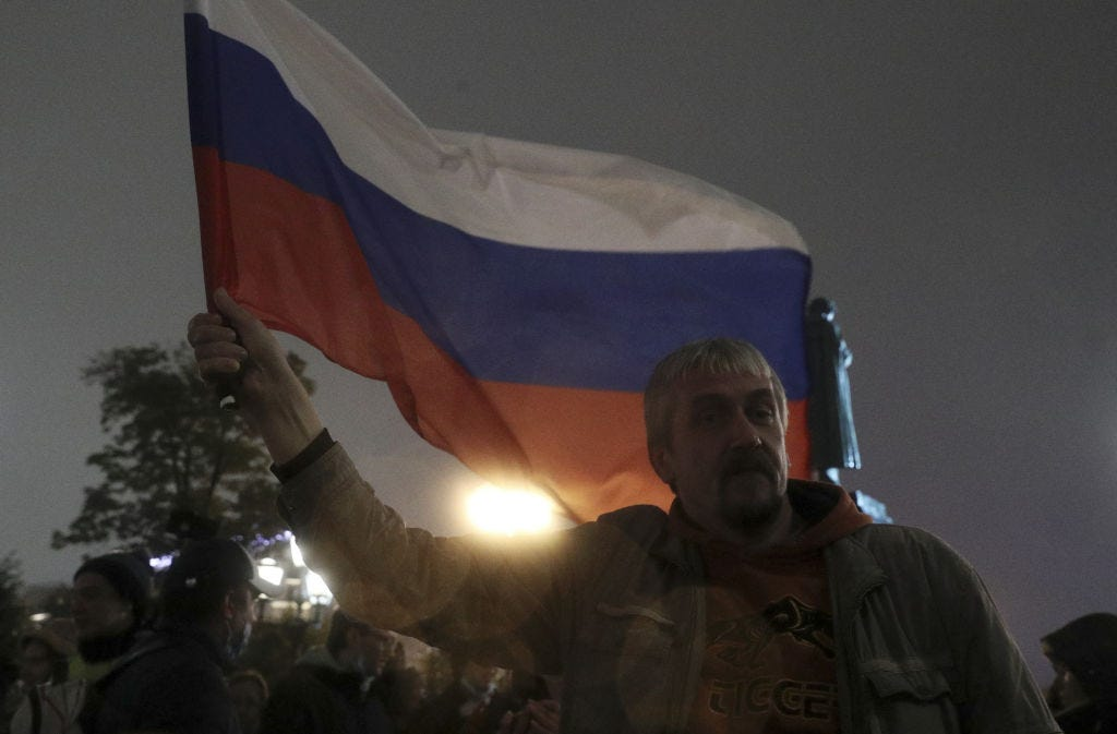 A demonstrator holds a Russian national flag during an unsanctioned protest in central Moscow against the results of the 2021 Russian parliamentary election. / (Alexander Shcherbak / Getty Images)