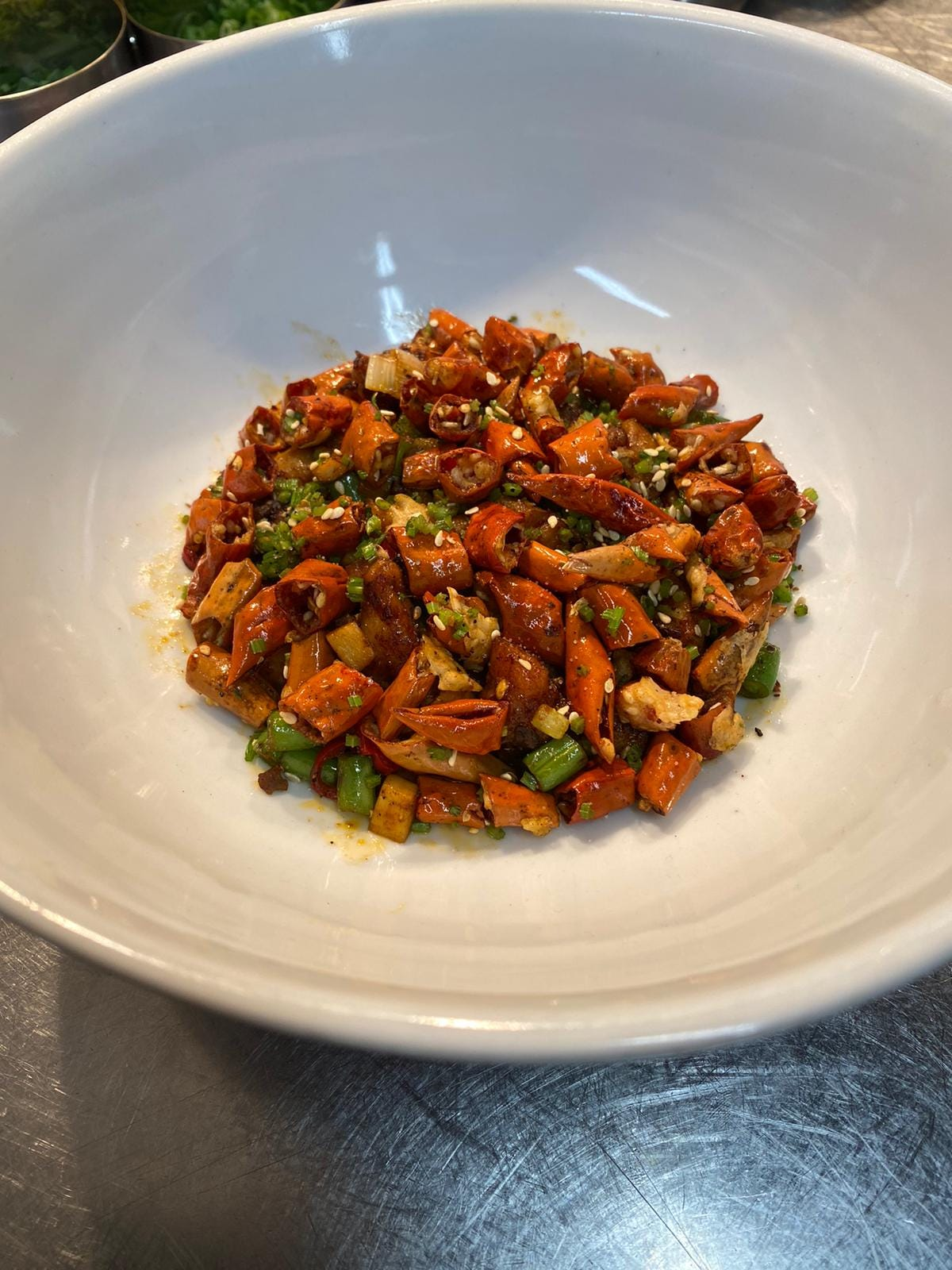 an overhead shot of a white dish on a stainless steel surface. In the dish is a pile of cooked red chillies, herbs, vegetables and chicken.