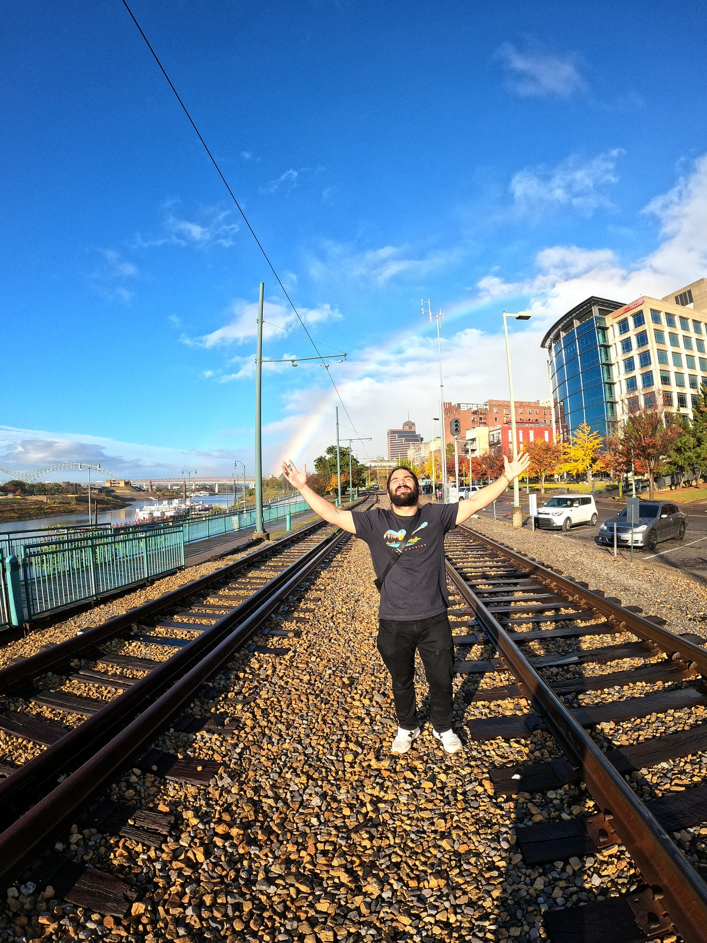 anthony under a rainbow on the train tracks with his arms stretched out