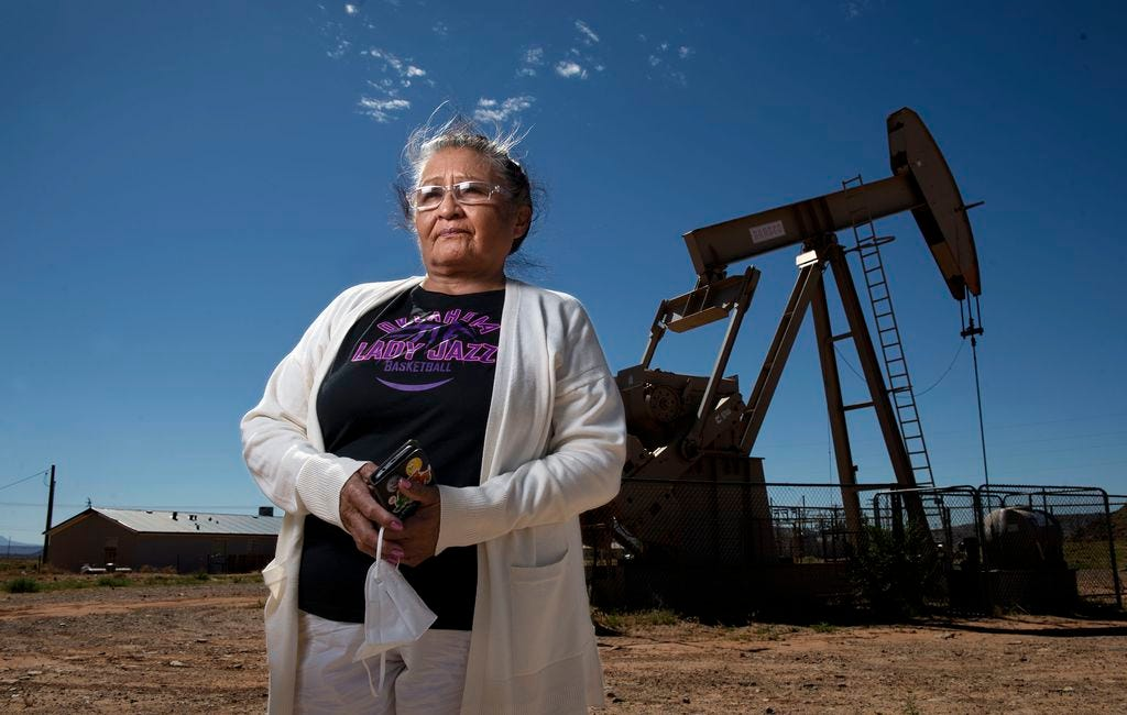 """(Leah Hogsten     The Salt Lake Tribune) """"People say open the doors, open the windows and get some fresh air,"""" said Marilyn Holly, 66. """"We cannot do that."""" Holly, a Navajo Nation Red Mesa Chapter vice-president and advocate for clean air, water and soil poses in front of an Elk Petroleum oil pump jack not far from her home in Montezuma Creek, June 24, 2020. """"We live with all these [oil] spills and all the stench, year after year."""""""
