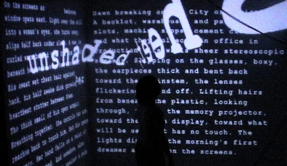 A silhouetted figure against a black wall of white words, two of which appear to be floating free.