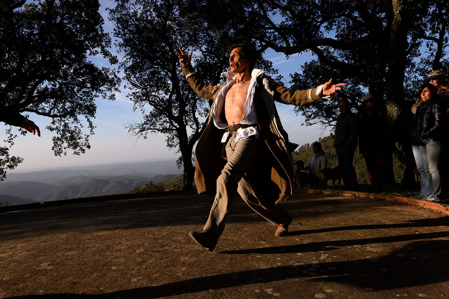 Dancer in spectacular Portuguese mountain setting watched by audience members.