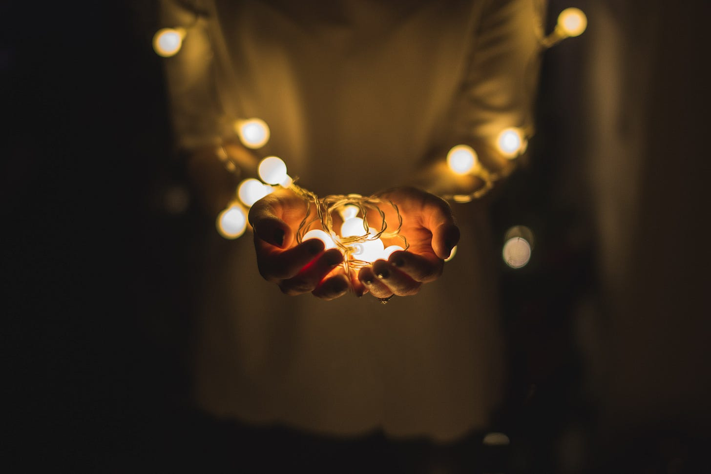hands holding illuminated string lights