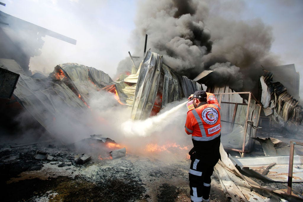A Palestinian firefighter puts out a fire at a sponge factory after it was hit by Israeli artillery shells. (Ahmed Zakot / Getty Images)