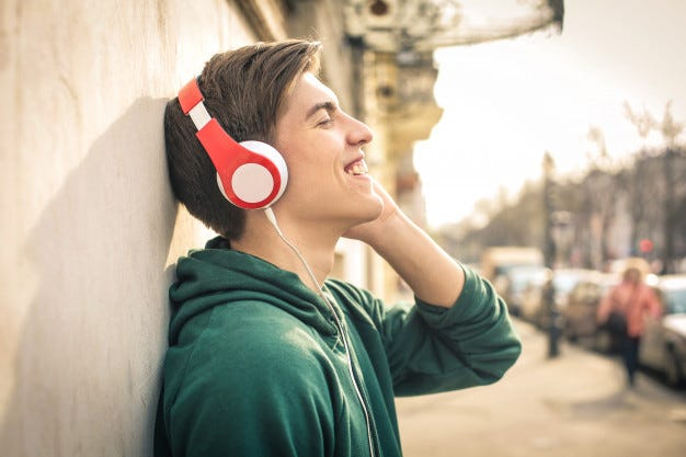 Teenager standing in the street, listening music with headphones Premium Photo