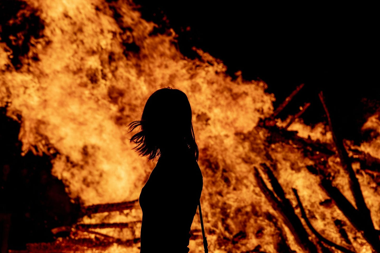 Image of fire burning with long-haired person profiled from behind, seeing just their outline