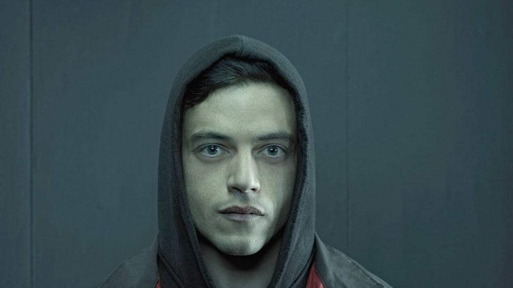 """Elliot Alderson, the """"Cypherpunk"""" in the fictional show """"Mr. Robot."""" He joins a group that aims to destroy all debt records by encrypting the financial data of the largest conglomerate in the world, E Corp."""