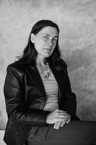 Picture of Mette Ivie Harrison. The picture is in black and white. She has dark shoulder-length hair and is looking at the camera with her hands folded in her lap. She is wearing a black leather jacket, jeans, a lighter shirt, and a necklace in the shape of leaves.