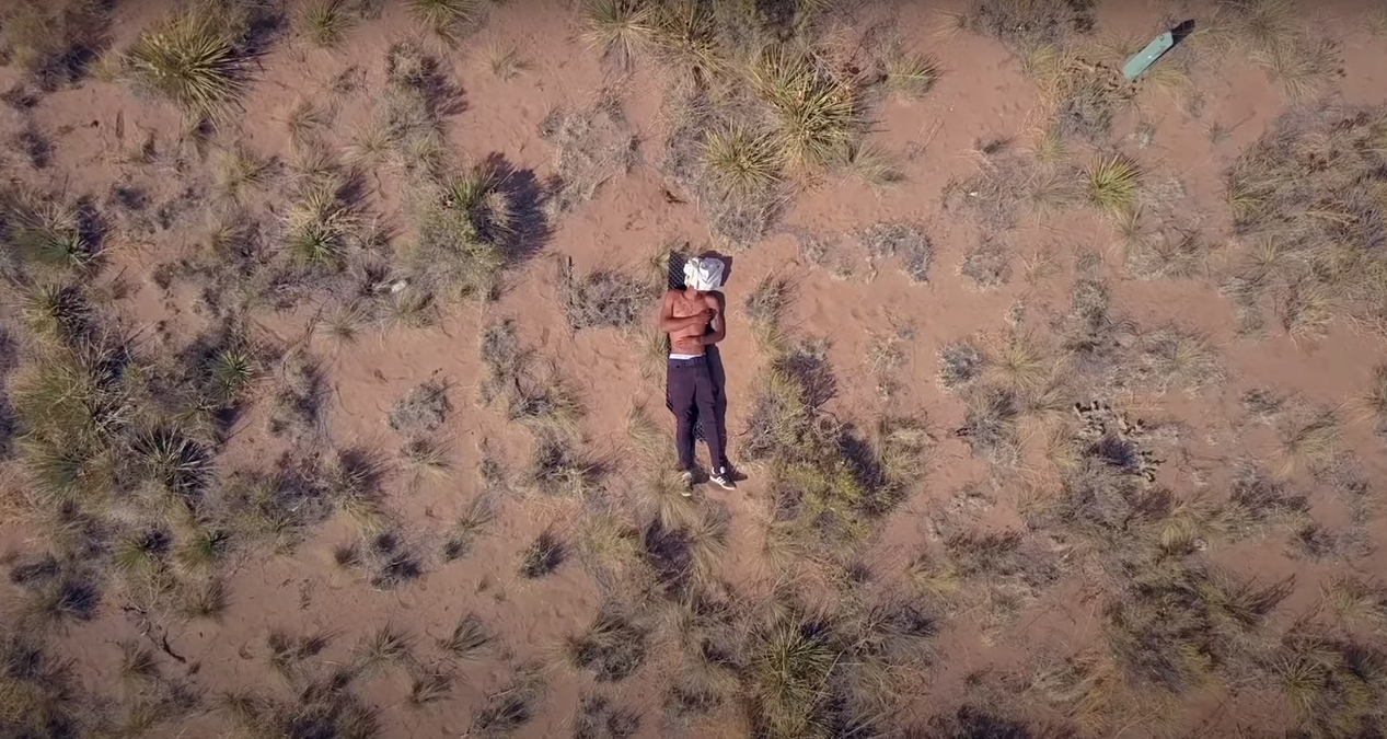 A camera looks to the ground from above at a shirtless man, laying face up, resting in the Colorado nature. From the film 'Crestone'.