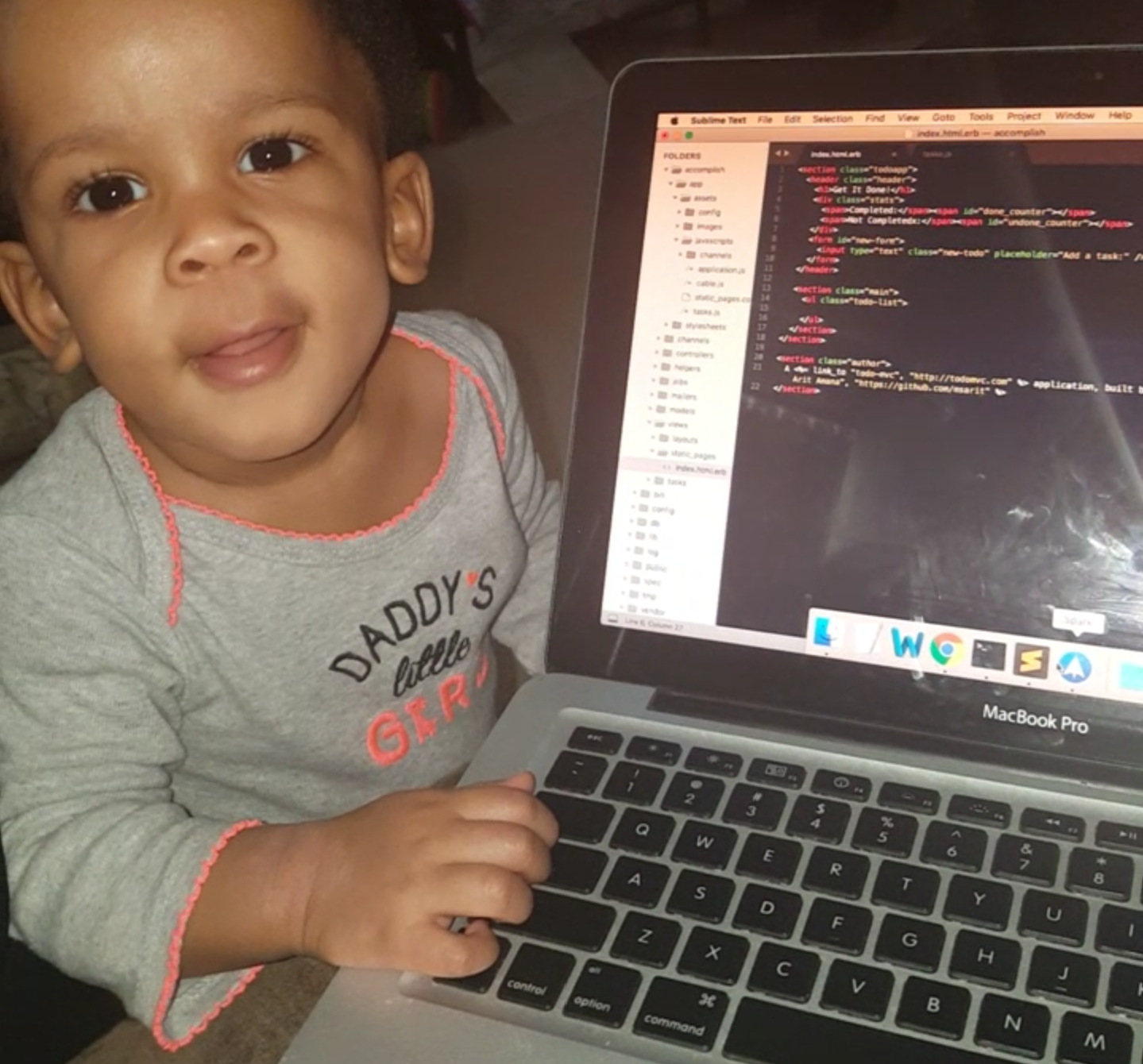 My macbook with some code displayed on the monitor, and my daughter on the right of the laptop, smiling with her hand on the keys.