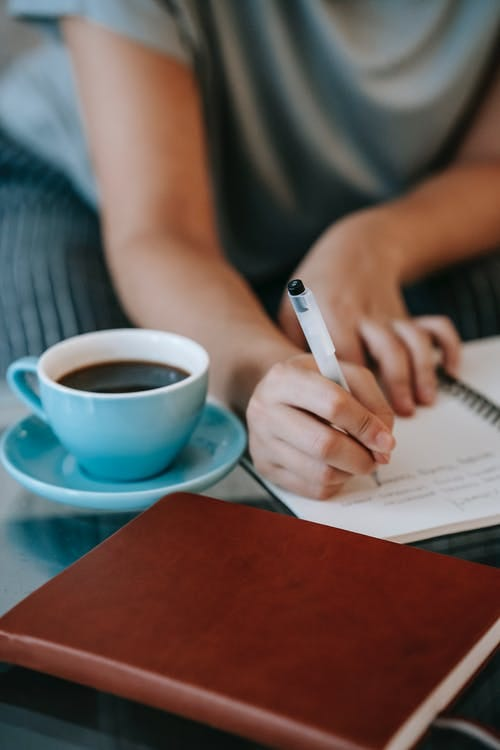 High angle of crop unrecognizable female author taking notes in diary and drinking cup of coffee while working remotely at home