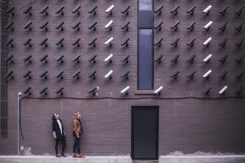 Two women looking up at a brick wall of fifty CCTV cameras.
