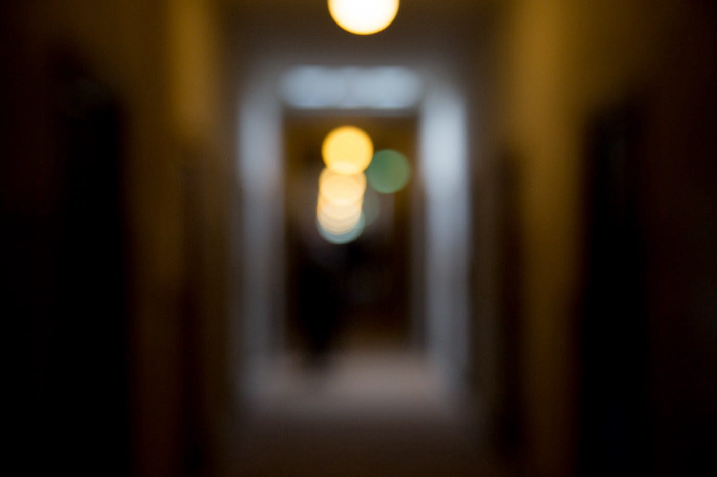 Blurry lights viewed down an out-of-focus hallway.