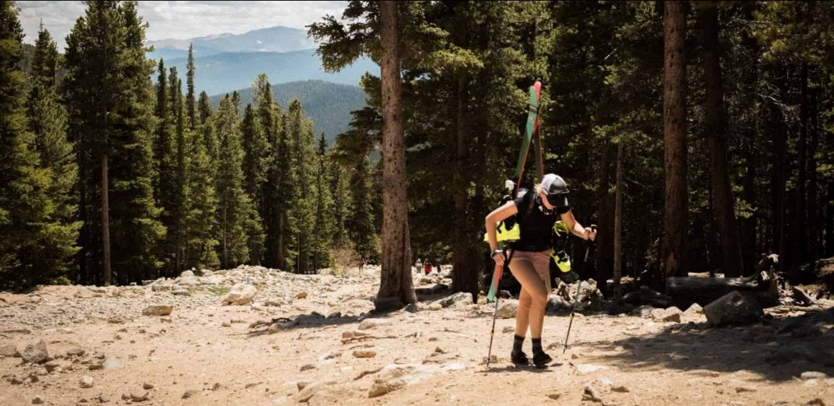 skier hikes up a colorado slope in the summer