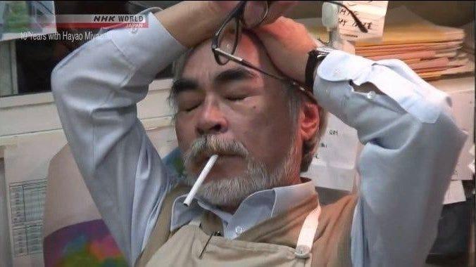 Cena do documentário, com Miyazaki, homem japonês de barba branca, camisa social e e avental, tirando os óculos e passando a mão na cabeça de olhos fechados. Na boca, um cigarro apagado.
