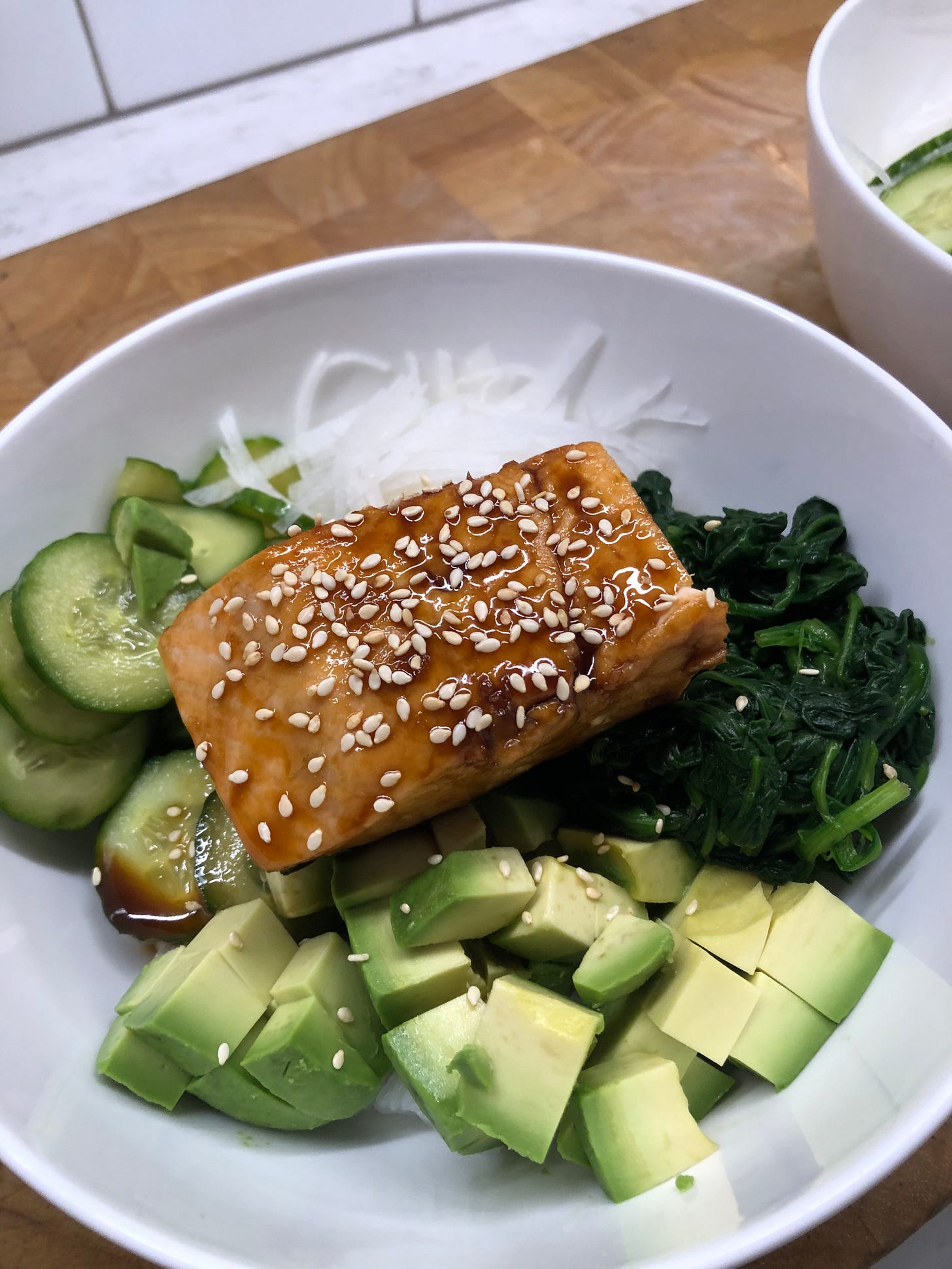A bowl of rice topped with salmon teriyaki, cucumbers, avocado, spinach, and daikon