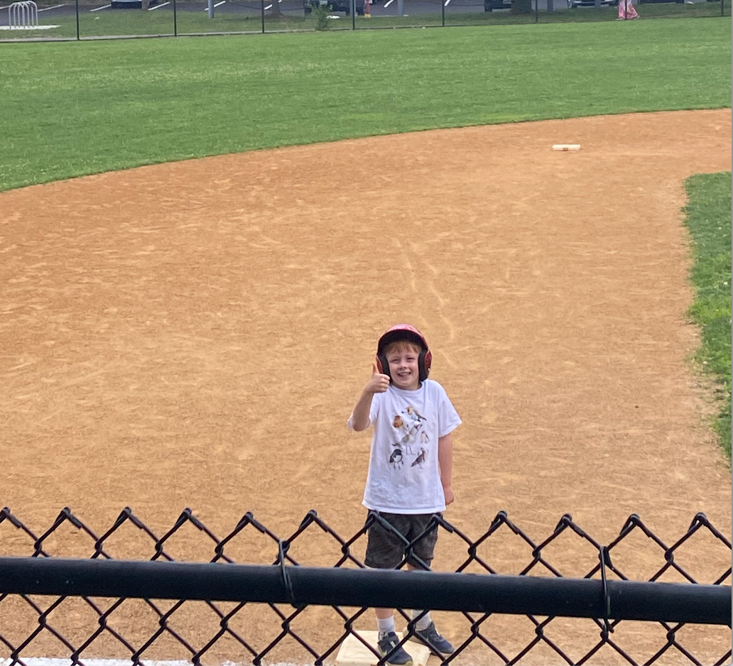 Seven-year-old giving a thumbs-up from the field.