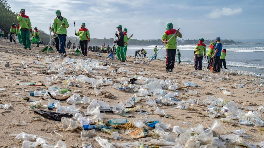 Workers clean up piles of debris and plastic waste brought in by strong waves at Kuta Beach in Bali, Indonesia, 01 January 2021.