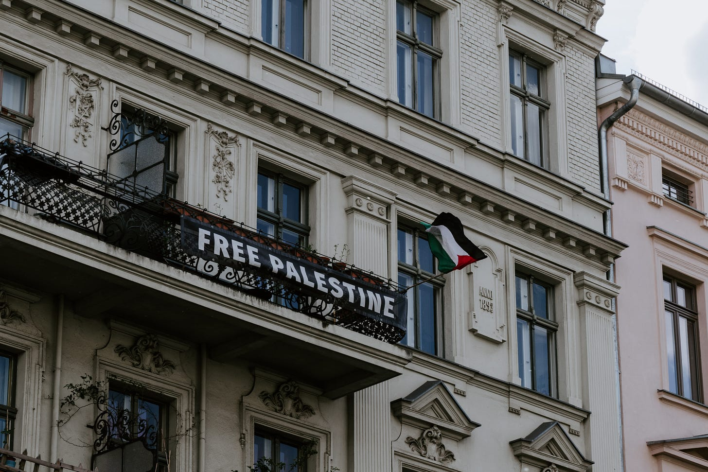 """A """"Free Palestine"""" banner hangs on a balcony."""