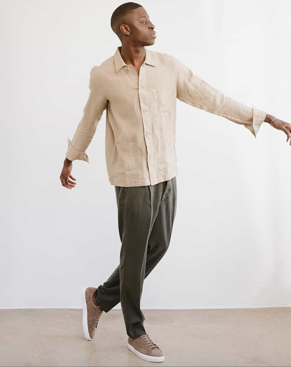 model struts while wearing a day's march linen overshirt in the khaki color