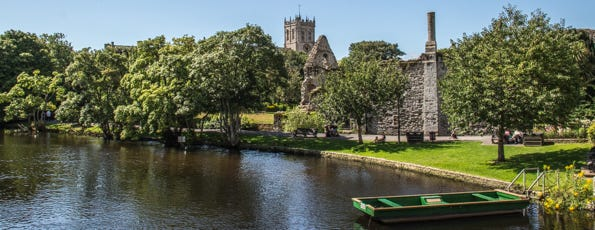 River next to castle ruins with a church in the background.