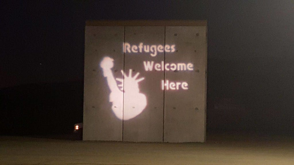 Refugees Welcome Here on Border wall with San Diego Solidarity Brigade Guerrilla Light Projection