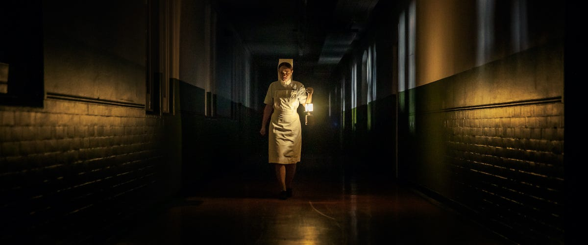 A nurse in a 1970s uniform walking down a dark hospital hallway with a lamp. She is centered in the frame, and the only source of light is from her lamp and some from the windows behind her.