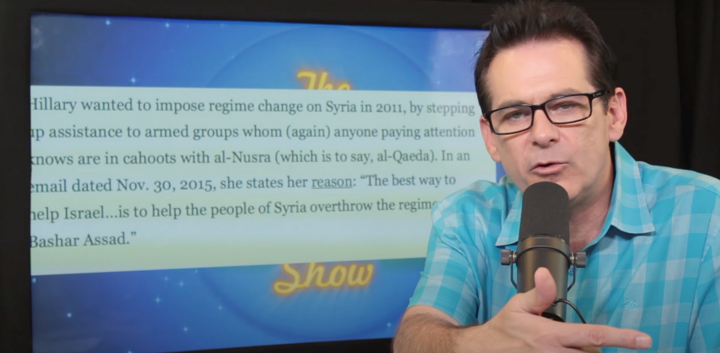 A man with glasses, a blue and white checkered shirt, and a microphone in front of a wall of text.
