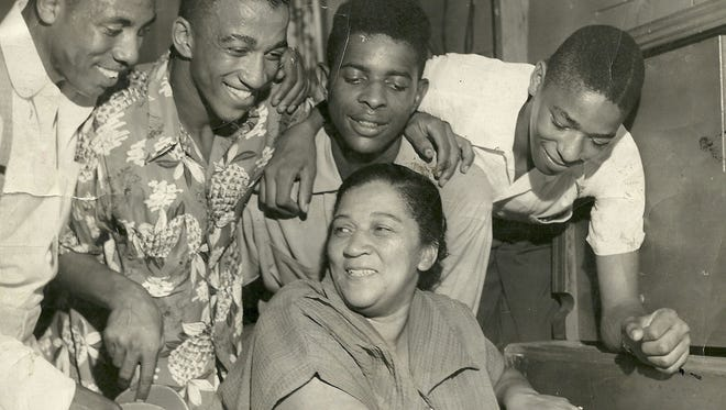 Willie Leola McQuany-Guess, center, is surrounded by her son Wellington and neighborhood youngsters in the Louisville Tigers den, which was a three-car garage converted into a youth clubhouse. She was politically active member of Smoketown. Photo circa 1953.