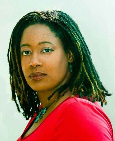 Angled portrait of N.K. Jemisin with a neutral expression on her face, looking to the camera, wearing a read shirt.