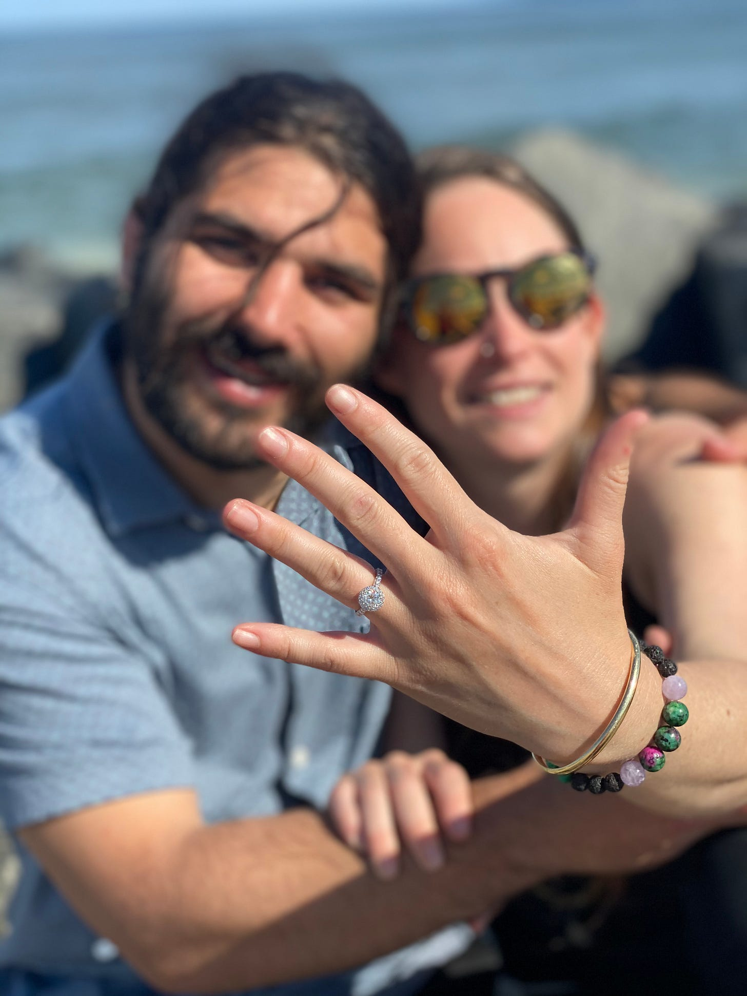 anthony and kelly pose engagement ring up