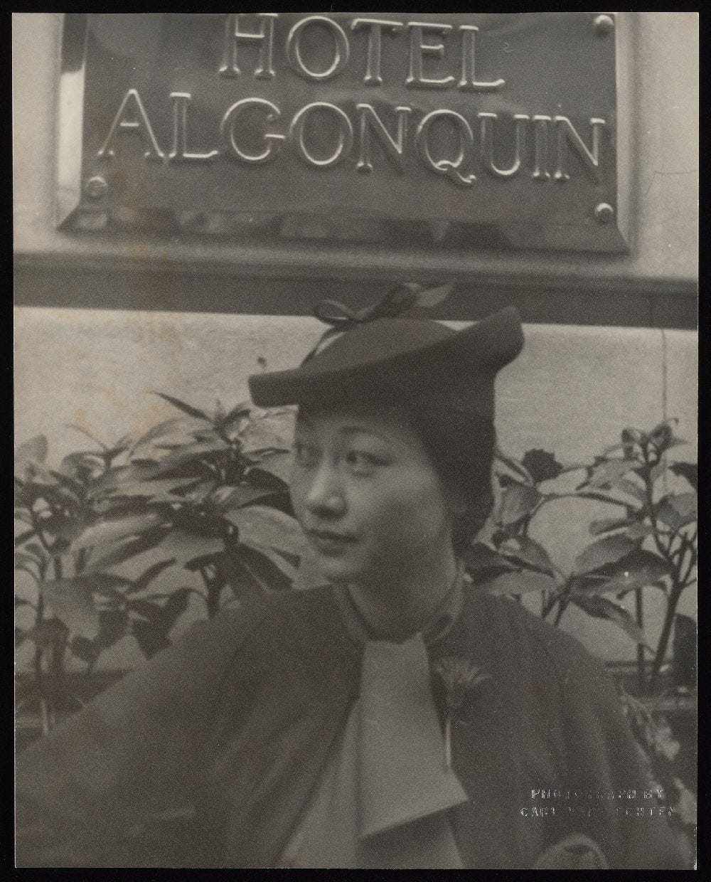 Anna May Wong looking spiffy in her hat, scarf, and a fresh flower pinned to her coat at the Algonquin Hotel, where she often stayed on trips to New York City.