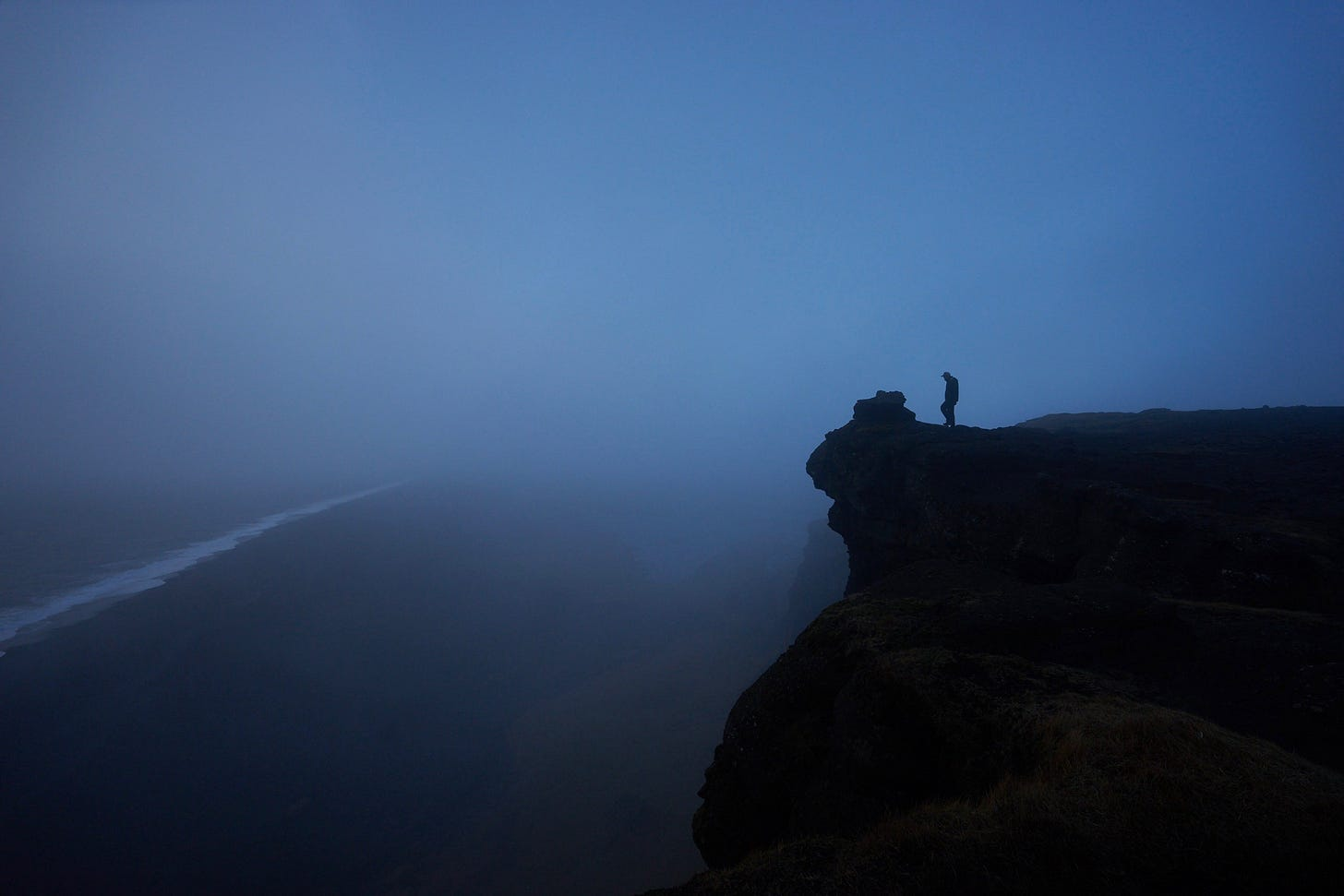 man on the edge of a cliff at night for article by Larry G. Maguire