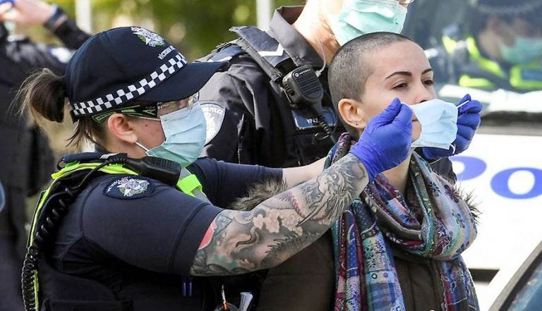 An Australian lockdown protestor gets Covid-masked by a police officer.