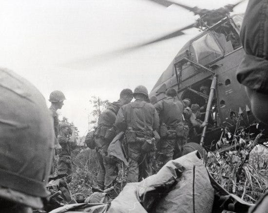 Black and white photo taken from a low position on the plant-covered ground. Military personnel huddle around the opening of a helicopter with blades spinning, loading someone in. Behind them, a young man in uniform is filming or photographing the scene.