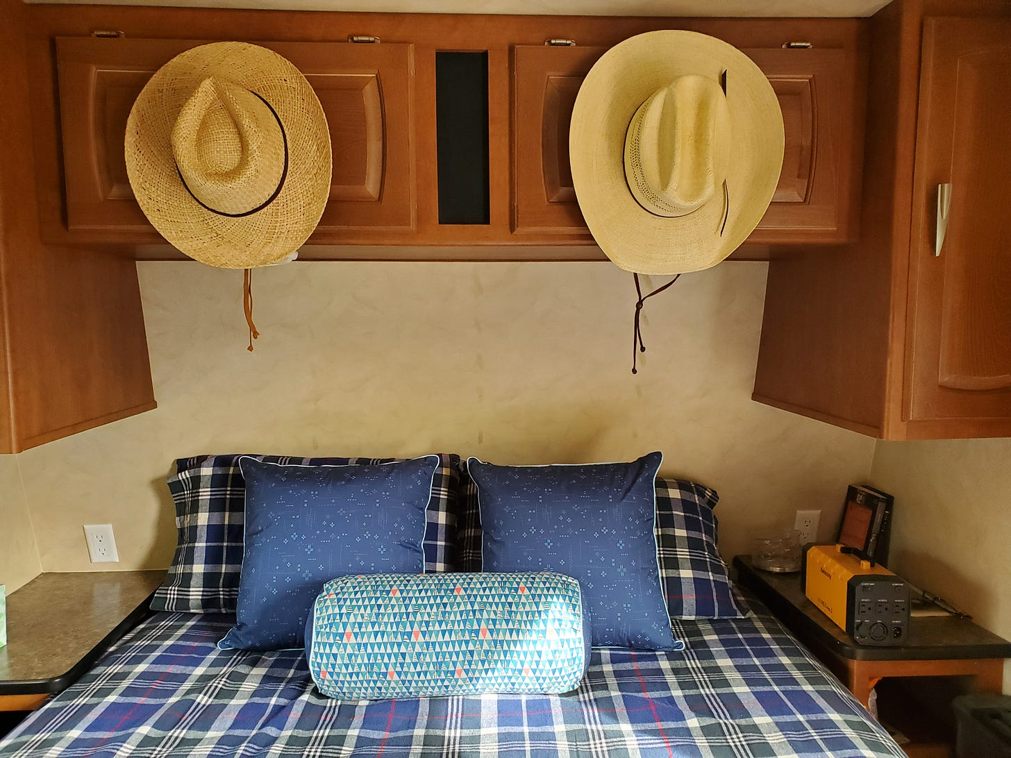 Interior shot of the travel trailer showing a queen bed with plaid sheets and pillows in various blue fabrics. Above the bed two cowboy hats hang his and hers style above from the upper cabinet.