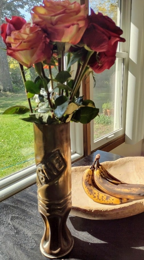 Flowers in vase with bananas in wooden bowl