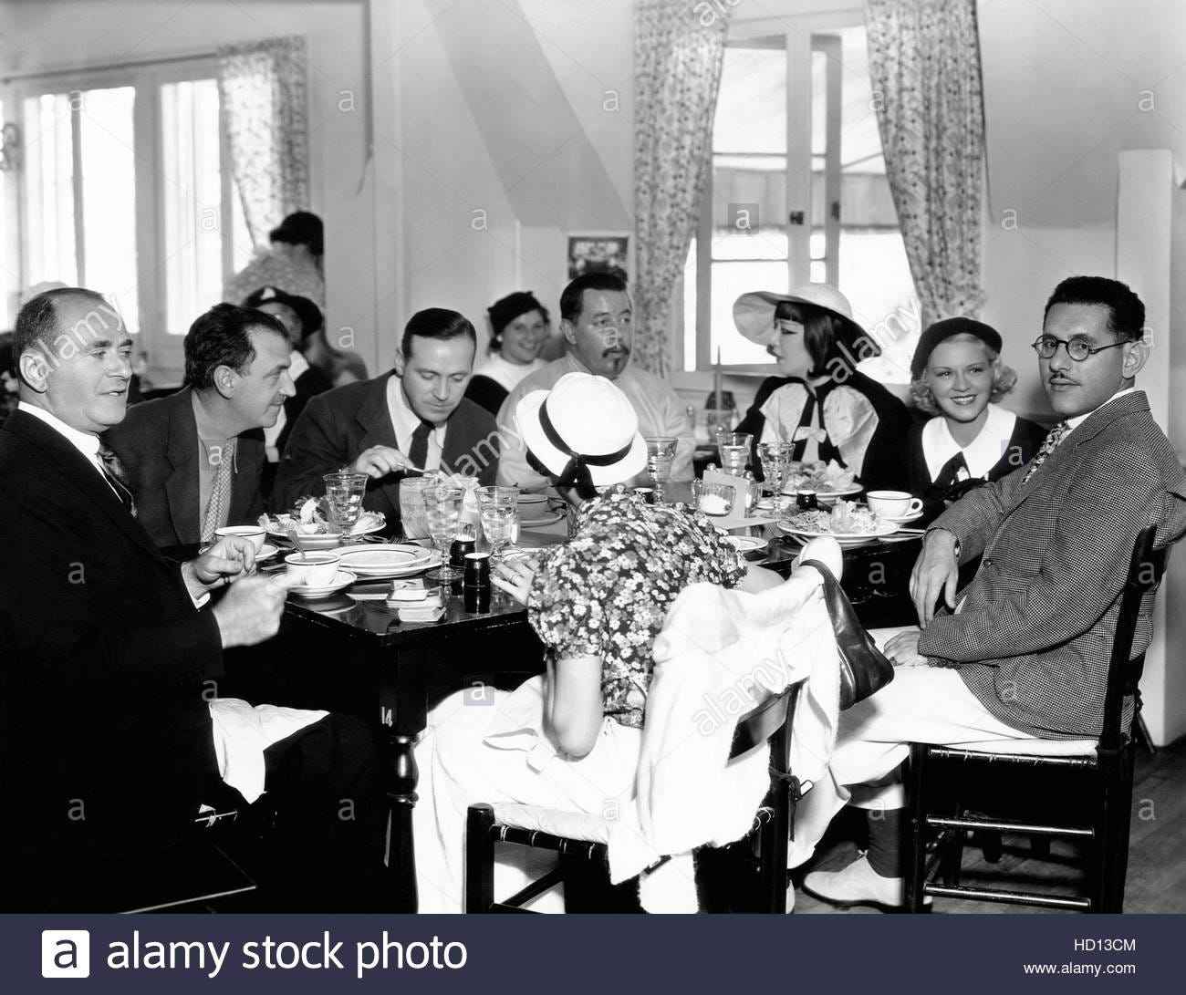 black and white photo of a group of film people at dinner, including Harry Lachman, Warner Oland, and Quon Tai Lachman