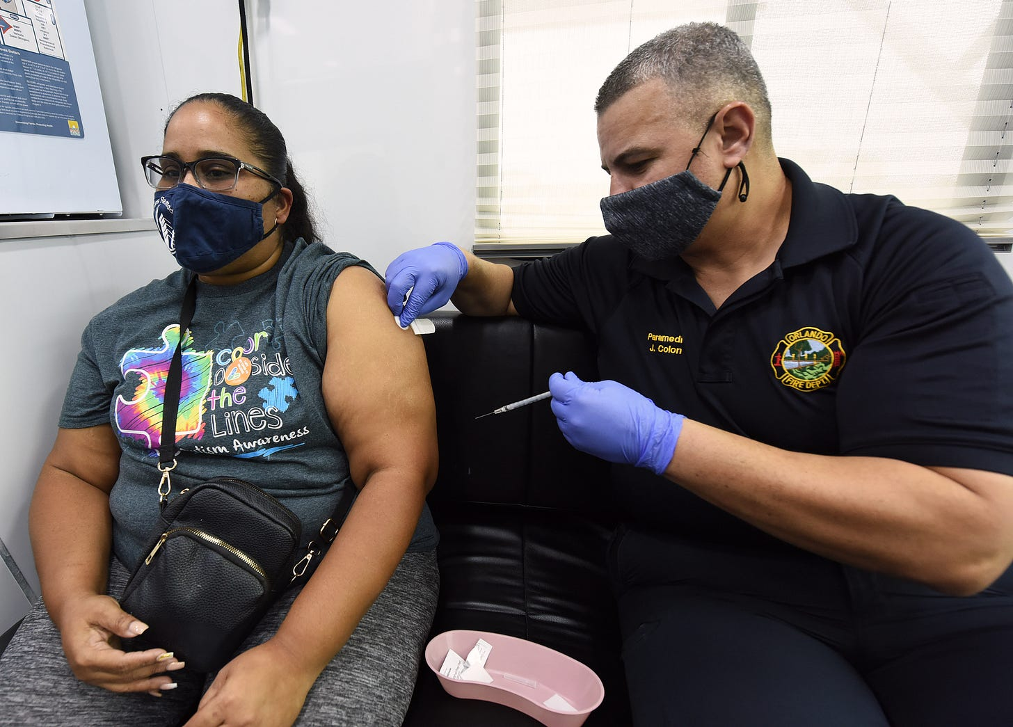 A man in an Orlando Fire Department polo holds a syringe and dabs the arm of a woman in a mask with alcohol, ready to administer the vaccine.