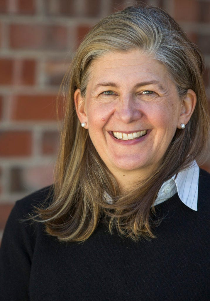 Author S. Kirk Walsh, a light skinned woman with sandy blond and gray hair down to her shoulders, is standing in front of a red brick wall wearing pearl earrings, a black sweater, a light blue striped shirt underneath.