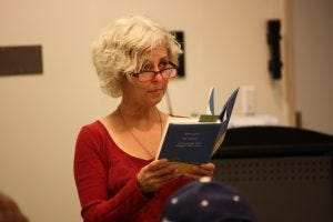 Photo of Kate DiCamillo standing and holding a book.