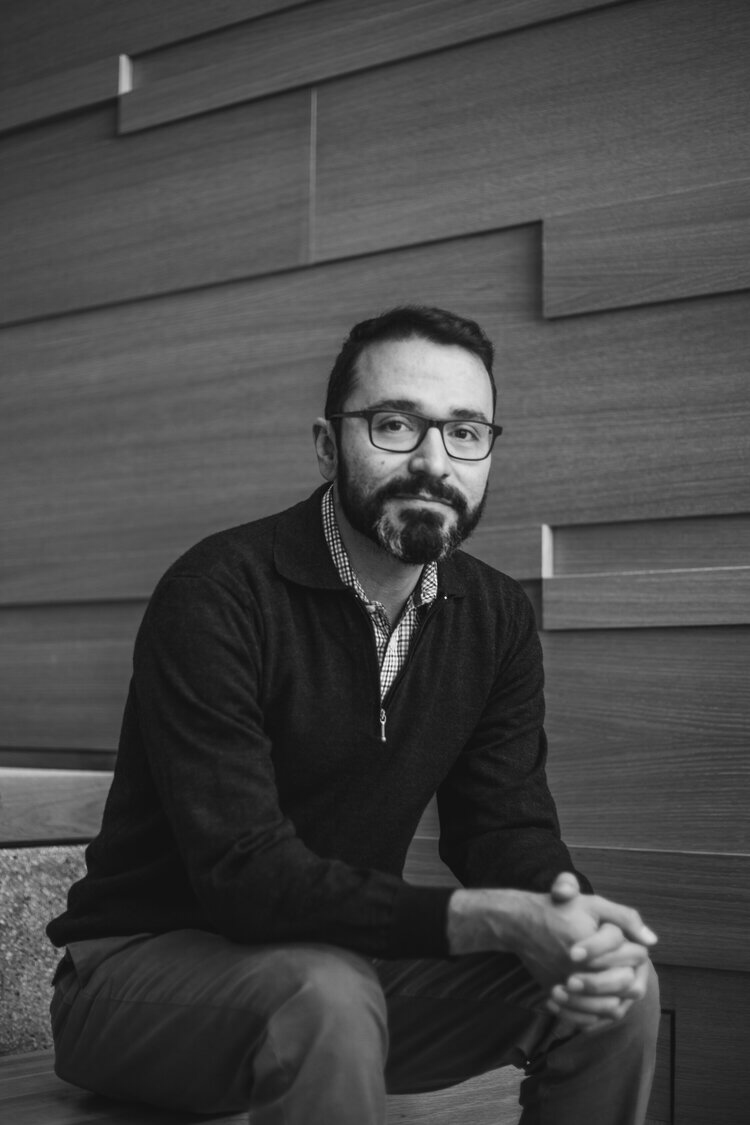 A black and white photo of a Mexican- American man with facial hair and glasses sitting down on a step. He's wearing a dark cardigan, a checkered collared shirt under it, and jeans. His hands are held together and he's leaning forward slightly with a soft smile.