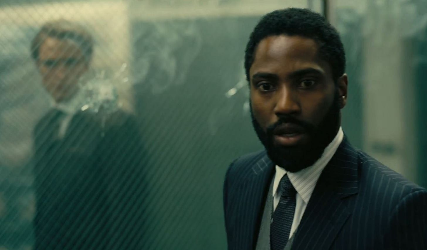 John David Washington in Tenet standing in front of a window with a bullet hole. On the other side of the glass is Robert Pattinson, watching him.