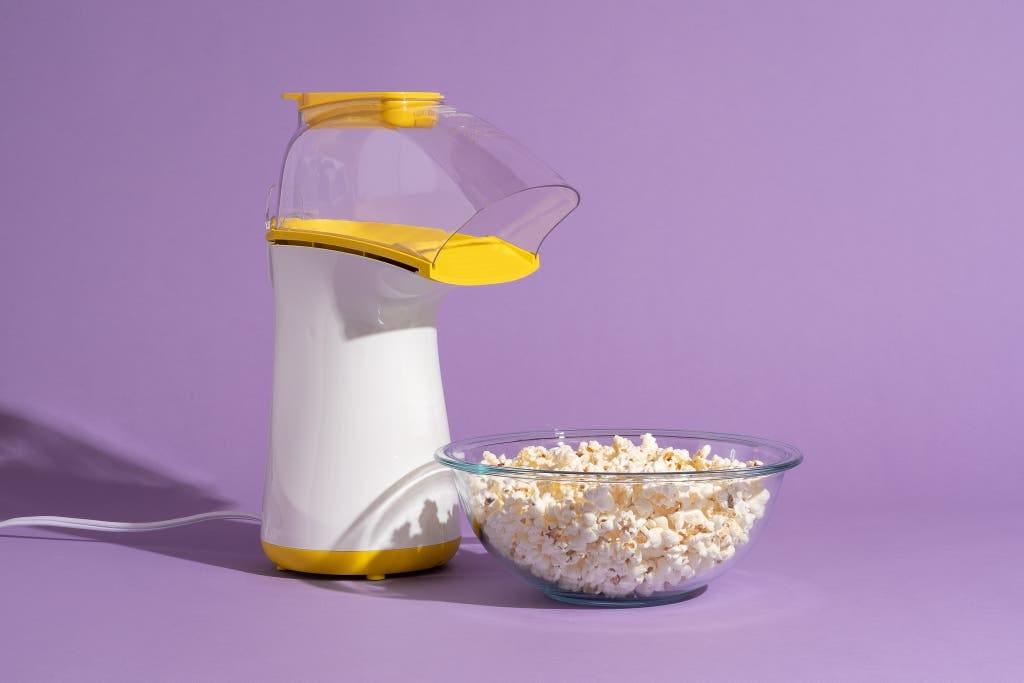 The air popper Presto PopLite next to a clear bowl full of popcorn