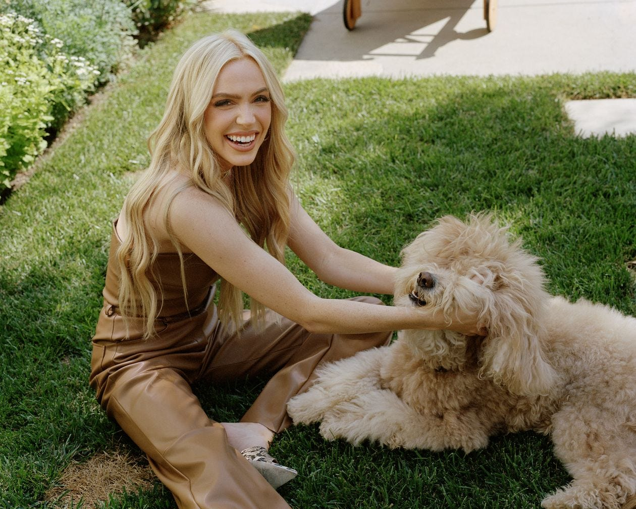 Picture of Alex Cooper, blond and smiling in brown leather pants and a leather tube top (?) sitting on a green lawn and scritching a very fluffy pup.